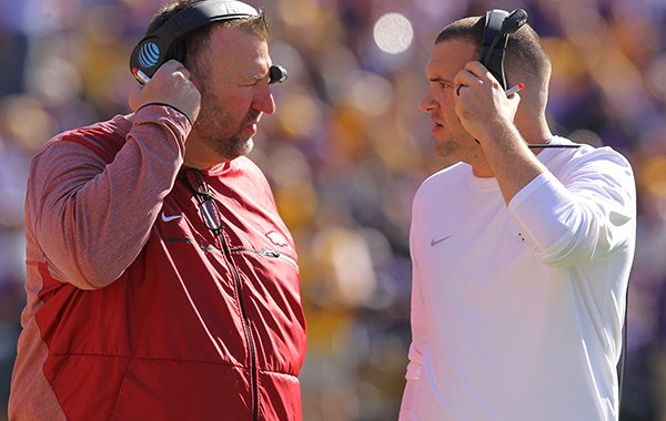 Arkansas coach Bret Bielema, left, talks with quality control coach Tanner Burns during a game against LSU on Saturday, Nov. 11, 2017, in Baton Rouge, La.