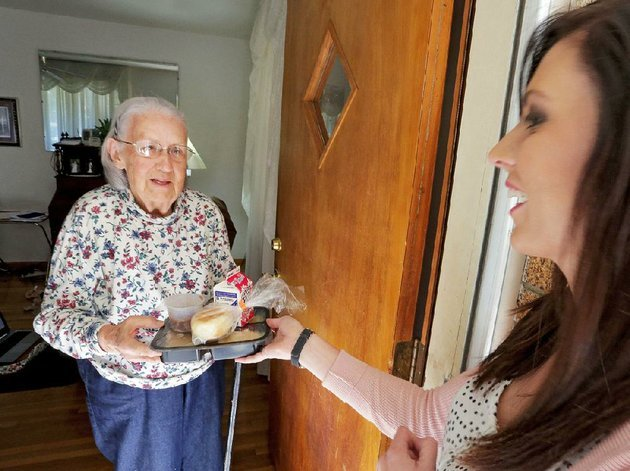 michelle-gilbert-outreach-and-marketing-officer-for-carelink-hands-a-meal-to-rosemary-meritt-82-oct-26-meritt-has-been-receiving-meals-on-wheels-for-about-a-year
