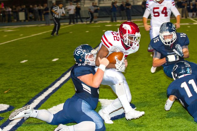 greenwoods-hunter-webb-53-drags-down-texarkanas-tyrie-black-22-as-greenwood-linebacker-travis-cox-15-moves-in-to-end-the-play-friday-in-greenwood