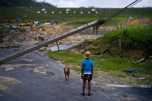 file-in-this-oct-17-2017-file-photo-a-boy-accompanied-by-his-dog-watches-the-repairs-of-guajataca-dam-which-cracked-during-the-passage-of-hurricane-maria-in-quebradillas-puerto-rico-experts-said-on-thursday-nov-16-2017-that-puerto-rico-could-face-nearly-two-decades-of-further-economic-stagnation-and-a-steep-drop-in-population-as-a-result-of-maria-ap-photoramon-espinosa-file