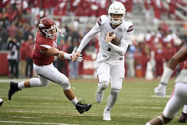 Mississippi State quarterback Nick Fitzgerald slips past Arkansas defender Grant Morgan to score a touchdown during the first half of an NCAA college football game Saturday, Nov. 18, 2017, in Fayetteville. (AP Photo/Michael Woods)