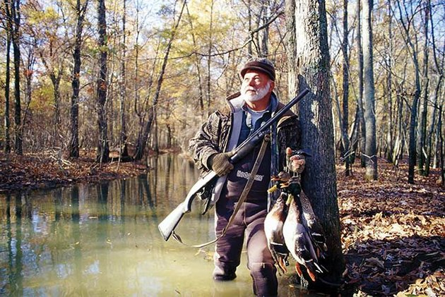 sammie-faulk-of-lake-charles-la-watches-for-ducks-in-flooded-timber-near-humnoke-arkansas-blue-ribbon-timber-hunting-attracts-waterfowlers-from-throughout-the-world