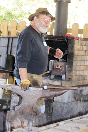 Pat Thompson explains the art of blacksmithing while working at the Ozark Folk Center in Mountain View. Thompson is the 2017 Crafter of the Year for the Folk Center.