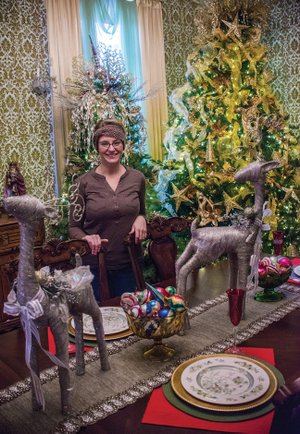 The Batesville home of Dustin and Monica St. John will be decorated with approximately 20 Christmas trees, including these in the dining room, which features wallpaper that is original to the house, built in 1921. Monica shown here, said each room will be decorated using various color-oriented themes.