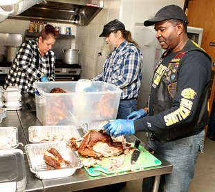 The Sentinel-Record/Richard Rasmussen TURKEY CARVING: Volunteers Melissa Allen, left, Jerry Allen and Emanuel Jernigal assist in preparing the Salvation Army's Annual Community Thanksgiving Dinner on Wednesday. The Salvation Army purchased 25 turkeys and projects they will feed approximately 250 for Thanksgiving.