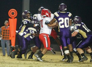 Terrance Armstard/News-Times Junction City's DaQuann Ford (21), Fred Daniel (55), Nathan Tucker (56), Jvacye Cook (20) and Brock McGoogan (18) lead a swarm of defenders trying to bring down Drew Central's Travarus Shead during their 6-3A contest earlier this month at David Carpenter Stadium. Tonight, Junction City hosts Clinton in a clash of undefeated teams in the 3A quarterfinals. Game time is set for 7 p.m. from Junction City.