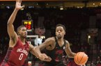 Arkansas guard Daryl Macon, right, drives to the basket as he is guarded by Oklahoma guard Christian James, left, during the second half in an NCAA college basketball game at the Phil Knight Invitational tournament in Portland, Ore., Thursday Nov. 23, 2017. (AP Photo/Troy Wayrynen)