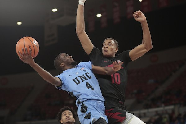 North Carolina's Brandon Robinson (4) drives on Arkansas's Daniel Gafford (10) in the second half of an NCAA college basketball game during the Phil Knight Invitational tournament in Portland, Ore., Friday, Nov. 24, 2017. (AP Photo/Timothy J. Gonzalez)