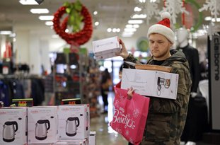 The Associated Press HOLIDAY SHOPPING: Joey Ellis adds to his armful of items while shopping for deals at a J.C. Penney store on Friday in Seattle. Black Friday has morphed from a single day when people got up early to score doorbusters into a whole season of deals, so shoppers may feel less need to be out.