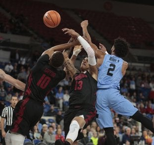 The Associated Press FREE FOR ALL: Arkansas' Daniel Gafford, left, and Dustin Thomas, center, fight North Carolina's Joel Berry II, left, for a loose ball in the first half of an NCAA basketball game during the Phil Knight Invitational tournament in Portland, Ore., Friday.