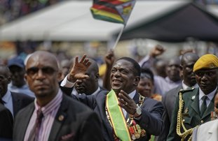 The Associated Press ZIMBABWE: Zimbabwe's President Emmerson Mnangagwa, center, gestures to the cheering crowd as he leaves after the presidential inauguration ceremony Friday in the capital Harare, Zimbabwe. Mnangagwa was sworn in as Zimbabwe's president after Robert Mugabe resigned on Tuesday, ending his 37-year rule.