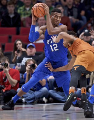 The Associated Press TAKING IT HOME: Duke forward Javin DeLaurier drives to the basket past Texas guard Eric Davis Jr. during the first half of an NCAA basketball game in the Phil Knight Invitational tournament in Portland, Ore., Friday.