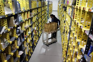 In this Dec. 22, 2015, file photo, Amazon Prime employee Alicia Jackson hunts for items at the company's urban fulfillment facility that have been ordered by customers, in New York. Shoppers are expected to spend $6.6 billion on Cyber Monday, up more than 16 percent from a year ago, according to Adobe Analytics, the research arm of software maker Adobe. And more people will be picking up their phones to shop: Web traffic from smartphones and tablets is expected to top desktop computers for the first time this year, Adobe said. (AP Photo/Mark Lennihan, File)