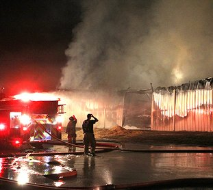 "The Sentinel-Record/Richard Rasmussen HAY BARN FIRE: Hot Springs firefighters work to contain a fire that erupted in a storage barn full of hay at 439 Broadway St. Monday night. The interior of the barn, belonging to Williams Brothers Feed Store, 401 Broadway, was ""fully involved"" when firefighters arrived, Fire Chief Ed Davis said. While they were able to get it under control, it was ""going to take a long time to overhaul"" everything."
