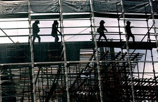 Construction workers walk on scaffolding Tuesday at a construction site Bangkok, Thailand. (AP Photo/Sakchai Lalit)