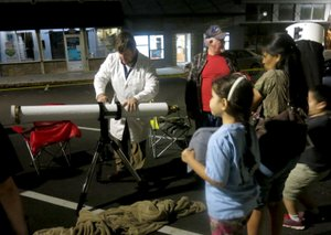 Photo by Susan Holland Van Masterson, events coordinator for NWA Space in Fayetteville, was on hand at the Gravette Public Library's star party Friday, Nov. 17, to explain the workings of the telescopes his group provided. Here he prepares to show Al Blair, Maria Pinto and her children Dina Teed and Paul Teed (partially hidden) how to use the finder scope he has set up. Dina holds one of the evening star maps provided to star party guests.