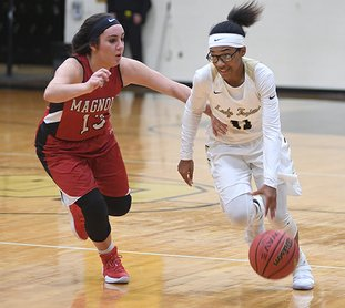 The Sentinel-Record/Mara Kuhn DRIVE IN: Hot Springs guard Kiah Beauford (11) drives past Magnolia's Kendall McMahen (13) Tuesday night at Trojan Fieldhouse. The Lady Trojans forced 19 turnovers in a 53-21 win.