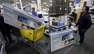 People wait to pay for televisions Nov. 23 as they shop a sale at a Best Buy store on Thanksgiving Day, in Overland Park, Kan. For the five-day period that ended the Monday after Thanksgiving, shoppers seemed to spend more in 2017 compared to a year earlier. (AP Photo/Charlie Riedel, File)