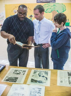 Anthony Wayne Hoskins, left, discusses some of the memorabilia from Pine Street School with Charles  Finkenbinder and his mother, Donna Velocci, who was visiting from New York and plans to retire in Conway. The three met recently in the old Pine Street High School gymnasium, which is on the grounds of the Greater Pleasant Branch Baptist Church, to discuss plans for the Pine Street Community Museum in Conway.