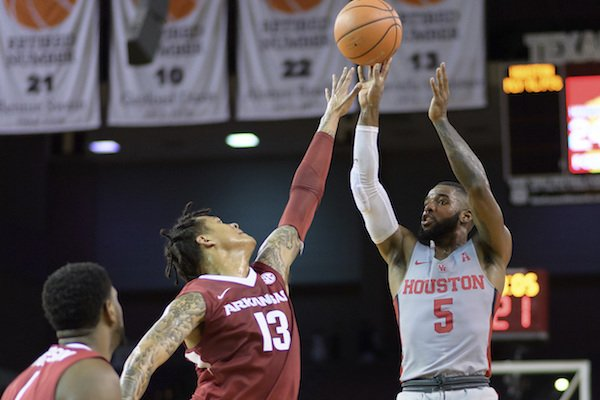 Houston's Corey Davis Jr. (5) takes a shot over the outstretched arms of Arkansas' Dustin Thomas (13) during an NCAA college basketball game, Saturday, Dec. 2, 2017 in Houston. (Wilf Thorne/Houston Chronicle via AP)