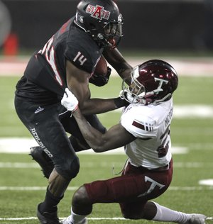 Troy cornerback Jawon McDowell (27) tackles Arkansas State wide receiver Chris Murray (14) during the second quarter of an NCAA college football game Saturday, Dec. 2, 2017, in Jonesboro, Ark. (Tommy Metthe/The Arkansas Democrat-Gazette via AP)