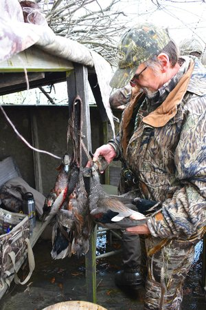 Glen Chase adds a gadwall to the strap Nov. 25 during a duck hunt in Arkansas County.
