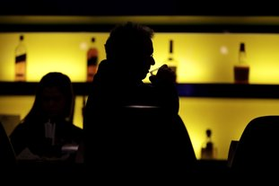 In this Nov. 30, 2017, photo, Dennis Dubrow, 62, Oceanport, N.J., takes a sip of his drink while having a meal at the William Hill Sports Bar in West Long Branch, N.J. The bar is located inside the Monmouth Park racetrack building. With banks of TVs tuned to all-sports stations and a spacious bar, the lounge is a sports gamblers paradise-in-waiting. All that's standing in its way: A 25-year-old federal law that bars betting on sports in most states. The high court is weighing On Dec. 4, whether a federal law that prevents states from authorizing sports betting is constitutional. If the Supreme Court strikes down the law, giving sports betting the go-ahead, dozens of states could quickly make sports betting legal. (AP Photo/Julio Cortez)