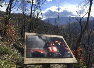 In this Nov. 21, 2017 photo, a placard on the Memorial Forest Walk at Anakeesta adventure park in Gatlinburg, Tenn. The Memorial Walk includes photos and stories of the wildfires that killed 14 people and destroyed or damaged 2,500 buildings in the Gatlinburg area last November. Work had just begun on Anakeesta when flames roared through its land. The $30 million Gatlinburg resort opened in September, with $8 million in additions planned. (AP Photo/Jonathan Mattise)