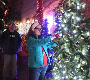 The Sentinel-Record/Mara Kuhn - Jade Snow places an ornament on the Memory Tree at Adair Park on Friday, Dec. 1, 2017. The public was invited to hang ornaments in memory of a loved one who has passed away or loved ones on active duty in the military during the holidays.