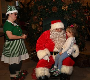 The Sentinel-Record/Mara Kuhn - Ana Blaise Rebsamen, 2, of Hot Springs visits with Santa as Elf Daphne Emery assists during the Arlington Resort Hotel & Spa's annual Gingerbread House Celebration on Friday, Dec. 1, 2017. The hotel served refreshments including hot coco, egg nog, and apple cider, along cookies and gingerbread. The Fun City Chorus also performed Christmas carols.