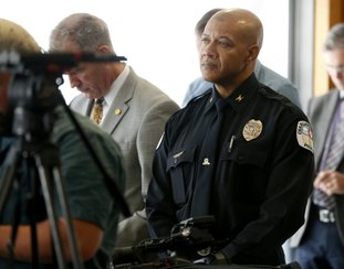 Charlottesville Police Chief Al S. Thomas Jr. listens to Attorney Timothy Heaphy as he delivers an independent report on the issues concerning the white supremacist rally and protest in Charlottesville, during a news conference in Charlottesville, Va., Friday, Dec. 1, 2017. (AP Photo/Steve Helber)