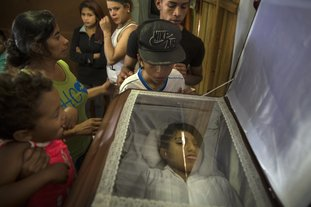 Family and friends gather around the coffin containing the remains of his sister Kimberly Dayana Fonseca, 19, in Tegucigalpa, Honduras, Saturday, Dec. 2, 2017. As the electoral count entered its sixth day Saturday, Fonseca was shot to death at a protest supporting opposition presidential candidate Salvador Nasralla by gunmen in two vehicles who witnesses say were police. (AP Photo/Rodrigo Abd)