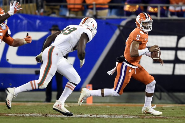 Clemson's Kelly Bryant (2) scrambles past Miami's Joe Jackson (99) during the first half of the Atlantic Coast Conference championship NCAA college football game in Charlotte, N.C., Saturday, Dec. 2, 2017. (AP Photo/Mike McCarn)