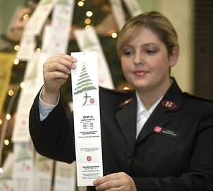 The Sentinel-Record/Mara Kuhn ANGEL TREE: Lieutenant Stephanie Hargis with The Salvation Army of Hot Springs presents a tag from The Salvation Army's Angel Tree on Saturday at the Hot Springs Mall. Hargis says over 200 angels still await adoption.