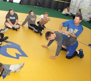 The Sentinel-Record/Richard Rasmussen DEMONSTRATING CONCEPTS: Lakeside High School wrestling coach H.E. Burchard, right runs a wrestling practice at the school during wrestling practice Friday.