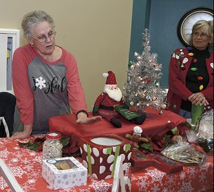 The Sentinel-Record/Mara Kuhn - Marilyn Hurst of Hot Springs sells baked goods at the Christmas Charity Bazaar at Hot Springs Baptist Church on Saturday, Dec. 2, 2017. The bizaar, which included several area vendors, raised funds for Recovery Point Ministry.