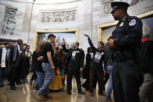 "The Associated Press CIVIL DISOBEDIENCE: With shirts saying ""fight poverty not the poor,"" people with the ""Poor People's Campaign"" gesture the group to remain quiet as the group leaves the Capitol Rotunda after praying in an act of civil disobedience in protest of the GOP tax overhaul, Monday, Dec. 4 on Capitol Hill in Washington."