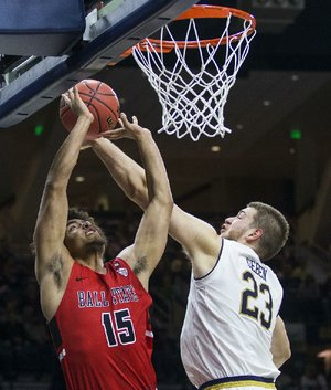 Ball State's Zach Gunn (left) goes up for a shot against Notre Dame's Martinas Geben during the Cardinals' 80-77 victory over the No. 9 Fighting Irish on Tuesday in South Bend, Ind.