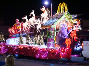 Westside Eagle Observer/RANDY MOLL Ronald McDonald rode in Santa's sleigh as he and the reindeer passed the Gentry Public Library in a past parade.