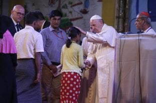 Pope Francis interacts with a Rohingya Muslim refugee at an interfaith peace meeting in Dhaka, Bangladesh, Friday, Dec. 1, 2017. Pope Francis ordained 16 priests during a Mass in Bangladesh on Friday, the start of a busy day that will bring him face-to-face with Rohingya Muslim refugees from Myanmar at an interreligious prayer for peace. (AP Photo/Aijaz Rahi)