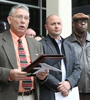 The Sentinel-Record/Richard Rasmussen FIGHTING CITY HALL: Doug Jones, left, president of the Watchmen of Garland County, reads a statement Tuesday in front of City Hall announcing the Concerned Citizens Coalition's intent to gather signatures in support of a referendum against the pending water rate increase. District 9 Justice of the Peace Matt McKee, center, and Difference Makers of Hot Springs President Willie Wade Jr. also spoke against the rate increase.