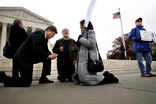 "The Associated Press PRAYING AND PROTESTING: Rev. Brad Wells, left, Rev. Patrick Mahoney, and Paula Oas, kneel in prayer in front of the Supreme Court, as a counter-protester holds a sign that says ""What's Christian About Discrimination,"" while the court hears the 'Masterpiece Cakeshop v. Colorado Civil Rights Commission' case, Tuesday in Washington."