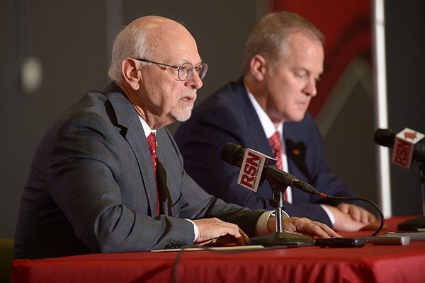 Joe Steinmetz (left), chancellor of the University of Arkansas, speaks Wednesday, Dec. 6, 2017, alongside Hunter Yurachek after Yurachek was introduced as the new director of athletics at the University of Arkansas during a news conference in the Fowler Family Baseball and Track Indoor Training Center in Fayetteville.