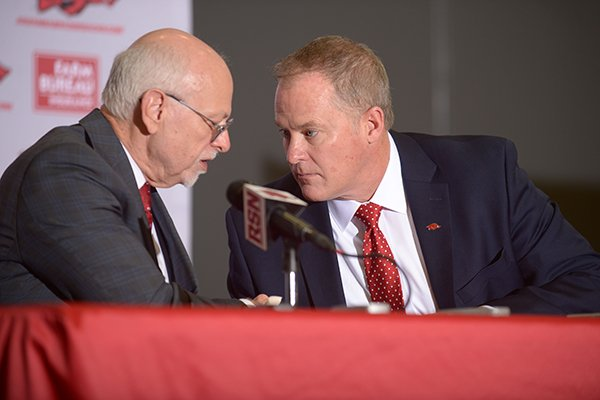 Joe Steinmetz (left), chancellor of the University of Arkansas, shakes hands Wednesday, Dec. 6, 2017, with Hunter Yurachek after Yurachek was introduced as the new director of athletics at the University of Arkansas during a news conference in the Fowler Family Baseball and Track Indoor Training Center in Fayetteville.