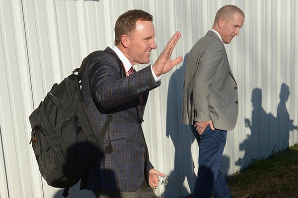 Arkansas football coach Chad Morris, left, waves to reporters after he landed at Drake Field in Fayetteville on Wednesday, Dec. 6, 2017. Morris was hired as the Razorbacks' 33rd football coach earlier in the day.