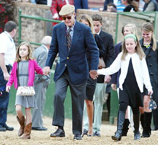 The Sentinel-Record/Richard Rasmussen FAMILY MAN: Owner Charles Cella, center, walks with family toward the infield saddling area prior to his horse Dyfly's victory in the Smarty Jones Stakes on Jan. 18, 2010, at Oaklawn Park. The longtime Oaklawn president died Wednesday at the age of 81.