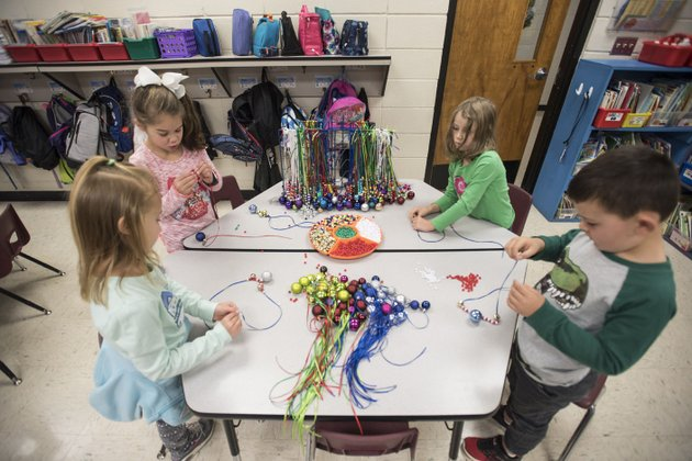 nwa-democrat-gazettespencer-tirey-kindergartners-analie-dryer-from-left-kendall-langley-kathryn-cooksey-and-blake-harris-work-on-making-jingle-bell-necklace-in-cristine-eubanks-class-at-thomas-jefferson-elementary-in-bentonville-this-is-the-third-year-students-have-done-the-project-to-raise-money-for-students-in-need-at-the-school-last-year-the-project-raised-about-1100