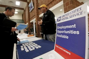 In this Nov. 2 photo, a recruiter from the postal service, right, speaks with an attendee of a job fair in Cheswick, Pa. On Thursday, the Labor Department reported that the number of unemployed workers filing for jobless benefits fell by 2,000 a week earlier to 236,000, the lowest level in five weeks and further evidence of the strength in the labor market. (AP Photo/Keith Srakocic)