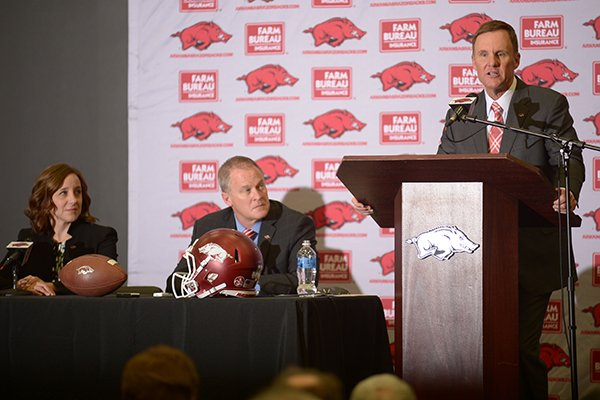 Arkansas football coach Chad Morris (far right) speaks while athletics director Hunter Yurachek (center) and former interim athletics director Julie Cromer Peoples look on during a news conference Thursday, Dec. 7, 2017, in Fayetteville.