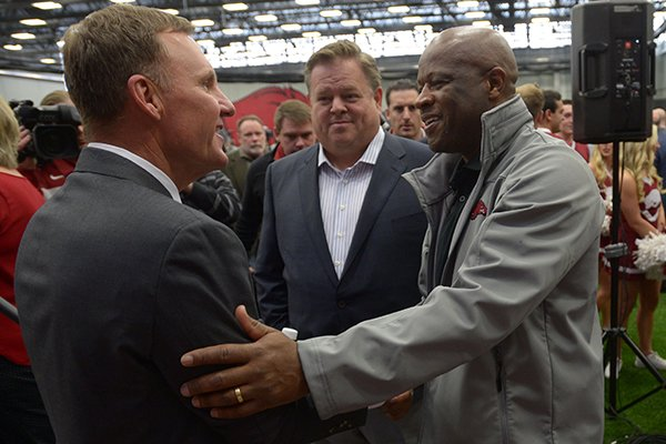 Arkansas football coach Chad Morris, left, is greeted by Arkansas basketball coach Mike Anderson, right, while agent Jimmy Sexton looks on following a news conference Thursday, Dec. 7, 2017, in Fayetteville.